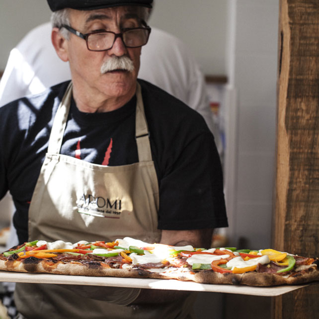 Man serving pizza in Cambridge restaurant